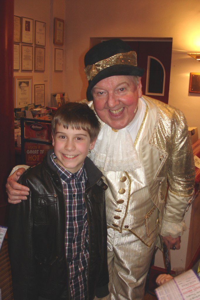 Jimmy poses with a child in the theatre foyer after one of the panto performances