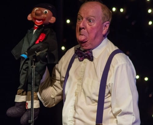 Jimmy Cricket performs on stage with a puppet